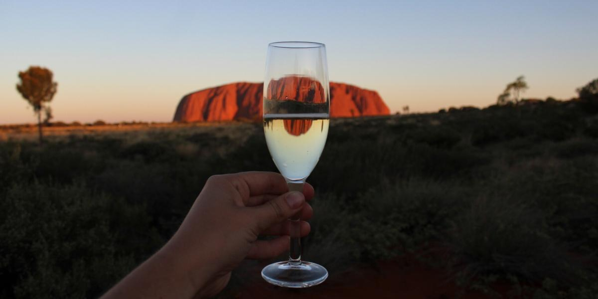 A large rock formation being reflected in a glass of low-carb wines
