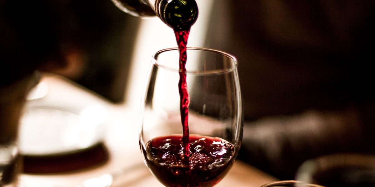Red Wine Being Poured Into a Stem Glass at the Table