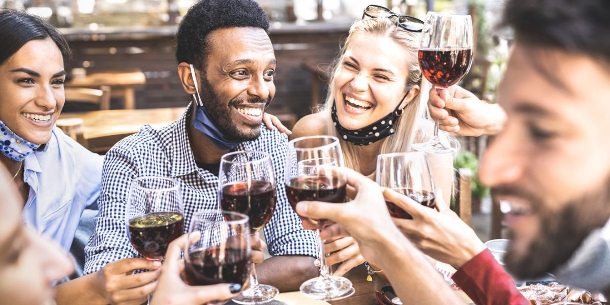Friends toasting red wine at outdoor restaurant bar with open face mask